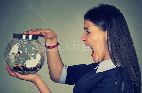 Angry woman holding a glass jar with a man working on laptop trapped inside Stock photo © ichiosea