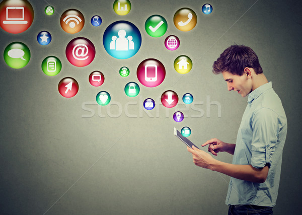 Stock photo: Mobile technology high tech concept. Side profile of a man using tablet computer with social media a