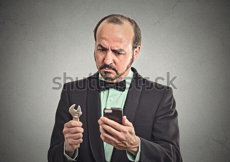 surprised businessman looking on smart phone holding calculator  Stock photo © ichiosea