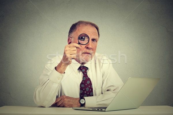 Serious business man in glasses skeptically looking through magnifying glass Stock photo © ichiosea