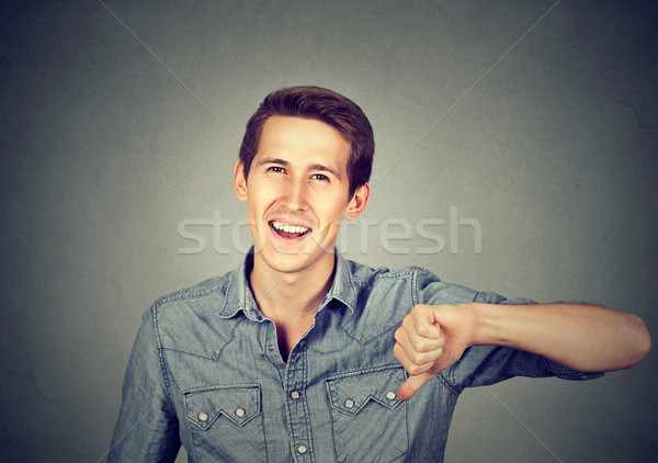 sarcastic man showing thumbs down, happy someone lost Stock photo © ichiosea