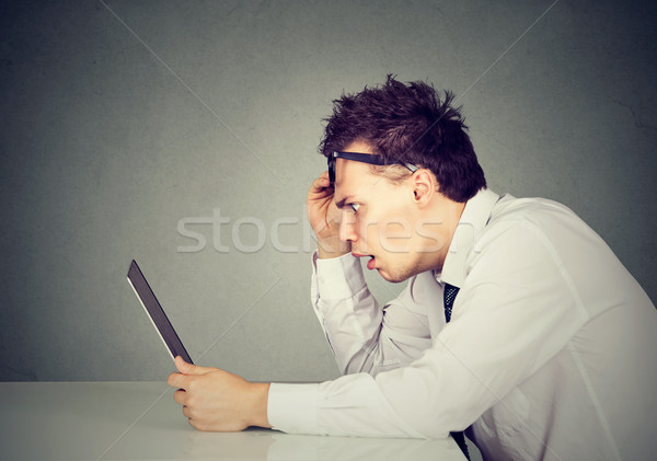 Side profile shocked man looking at laptop computer Stock photo © ichiosea