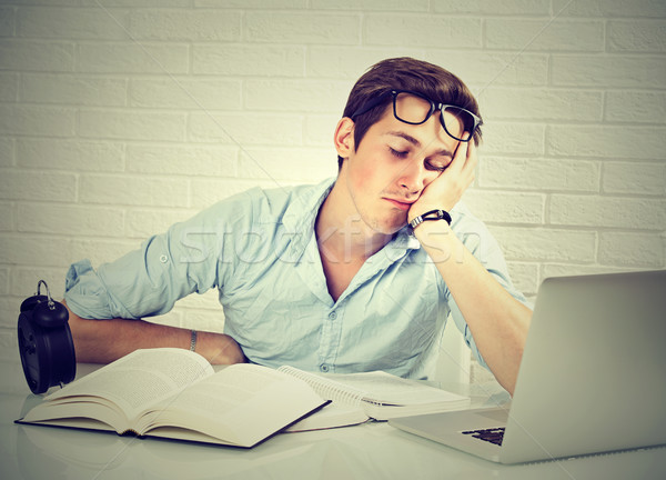 tired sleepy man sitting at desk with books in front of laptop Stock photo © ichiosea