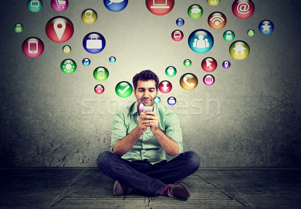 Man sitting on floor using smartphone application icons flying up Stock photo © ichiosea
