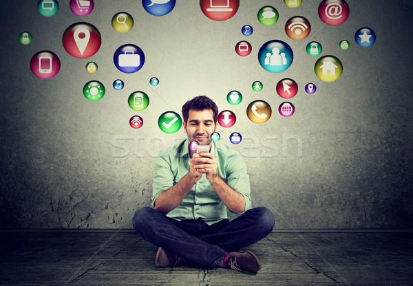 Férfi ül padló okostelefon alkalmazás ikonok Stock fotó © ichiosea