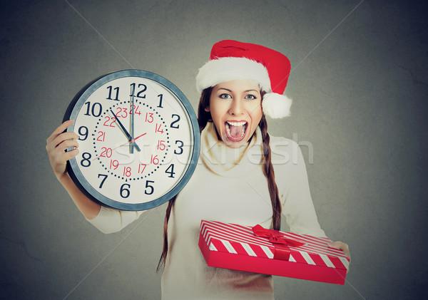 happy woman wearing red santa claus hat holding clock gift box  Stock photo © ichiosea
