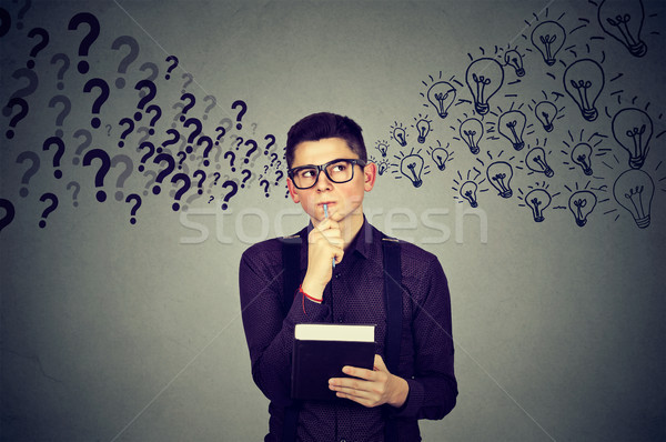 Young man finding answers to many questions generating ideas Stock photo © ichiosea
