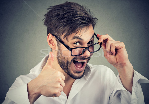 Stock photo: Young bearded man in glasses showing thumbs up