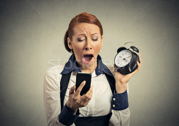 Stock photo: Sleepy woman with mobile smart phone and alarm clock