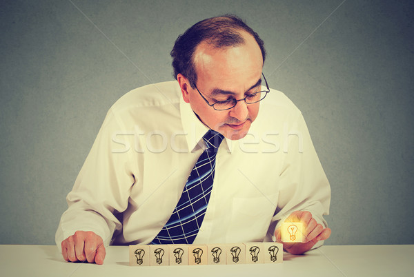 Middle aged business man sitting at table desk with yellow bright light bulb idea Stock photo © ichiosea