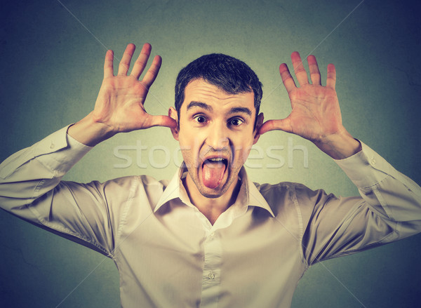 Young angry man, sticking out tongue at you, camera gesture Stock photo © ichiosea