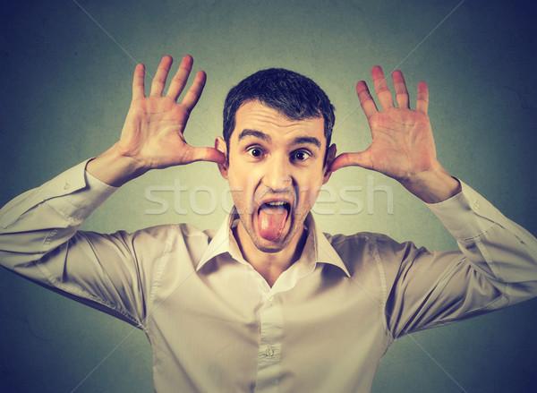 Jóvenes enojado hombre fuera lengua cámara Foto stock © ichiosea