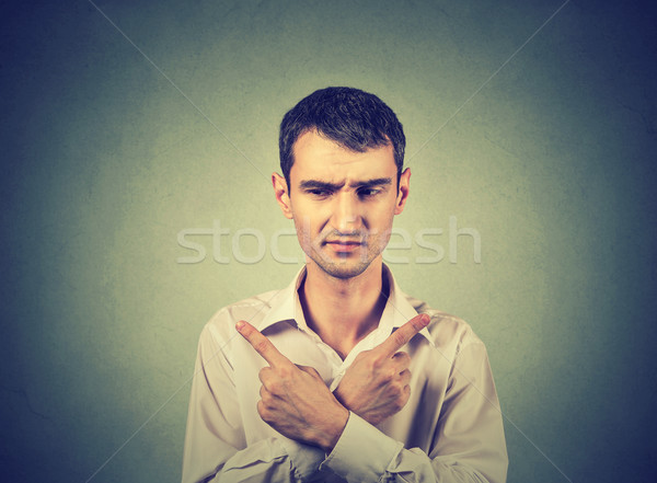Confused man pointing in two different directions, hesitant to make decision  Stock photo © ichiosea