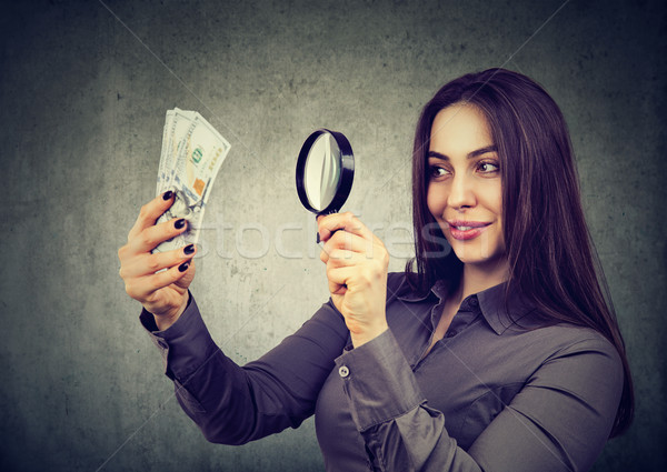 woman looking at one hundred dollar bills through magnifying glass  Stock photo © ichiosea