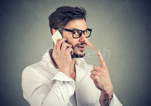 Stock photo: Man speaking on phone and lying