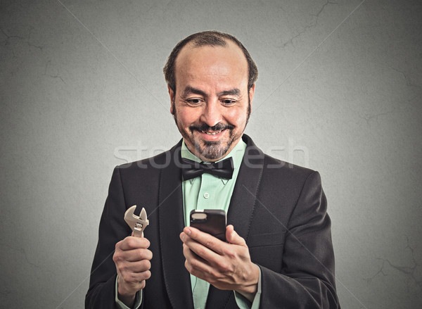 businessman looking at smartphone holding wrench tool Stock photo © ichiosea