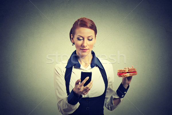 business woman reading news message on smart phone holding eating sandwich Stock photo © ichiosea