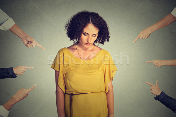 Accusation guilty person girl. Sad embarrassed woman looking down many fingers pointing at her Stock photo © ichiosea