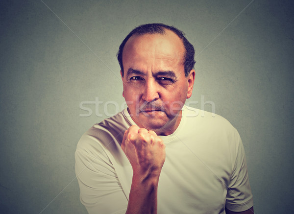 Middle aged angry man with fist up isolated on gray wall background  Stock photo © ichiosea