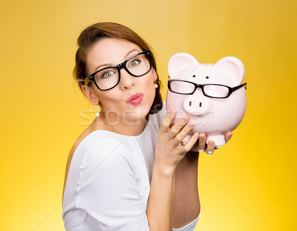 Glasses sale concept. Happy woman kissing piggy bank wearing eyewear glasses Stock photo © ichiosea