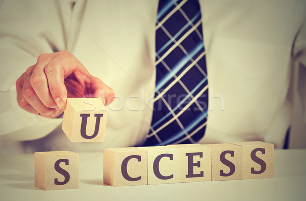 Successful businessman arranging wooden cubes reading success Stock photo © ichiosea