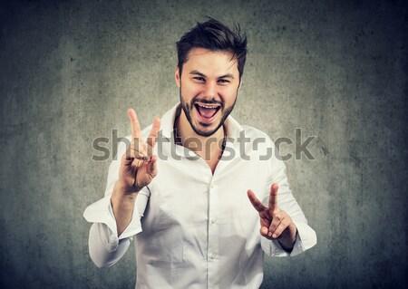 Plein d'espoir bel homme doigts isolé gris Photo stock © ichiosea