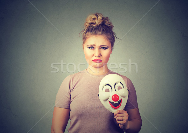 upset woman with sad expression holding clown mask expressing happiness Stock photo © ichiosea