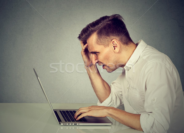 Side profile stressed man working on laptop sitting at table   Stock photo © ichiosea