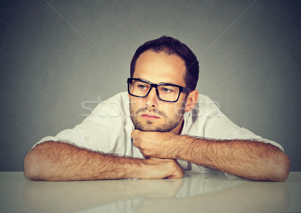 Desperate young businessman leaning on a desk Stock photo © ichiosea