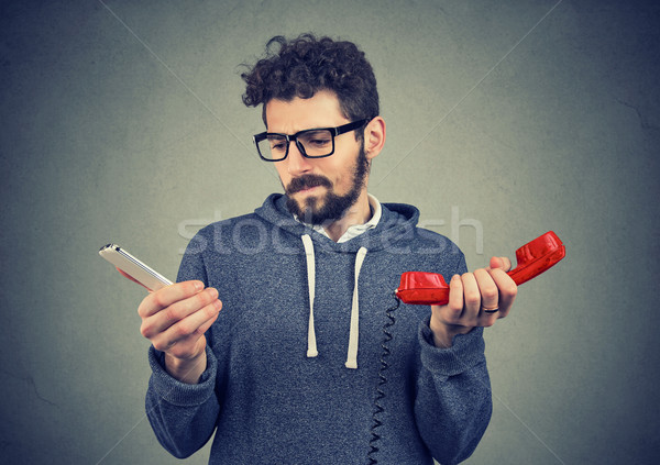 Confused man with old and new phones Stock photo © ichiosea