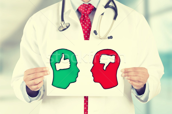 doctor hands holding card with thumbs up thumbs down symbols inside signs shaped as human head Stock photo © ichiosea