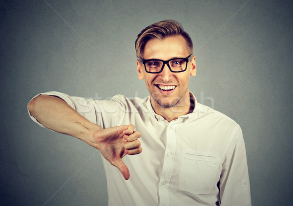 sarcastic man showing thumbs down sign happy someone lost failed Stock photo © ichiosea