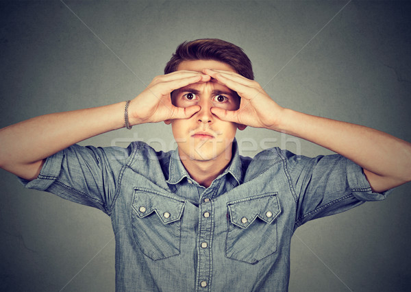 Stock photo: Serious man looking through hands shaped as binoculars