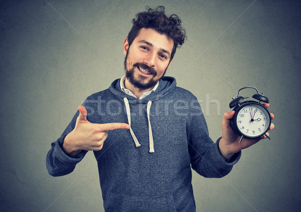 Stock photo: Young expressive happy hipster man holding alarm clock