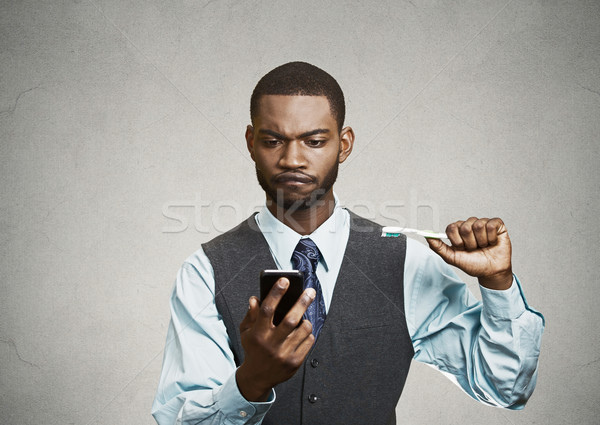 Busy life of an executive. Man holding smart phone, toothbrush Stock photo © ichiosea