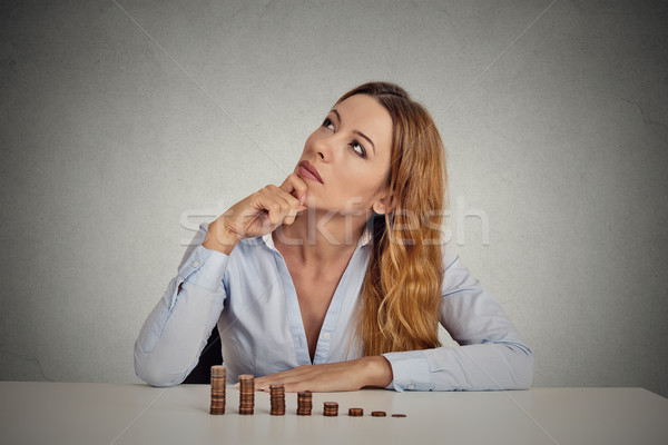 Stock photo: business woman corporate executive sitting at table with growing stack of coins