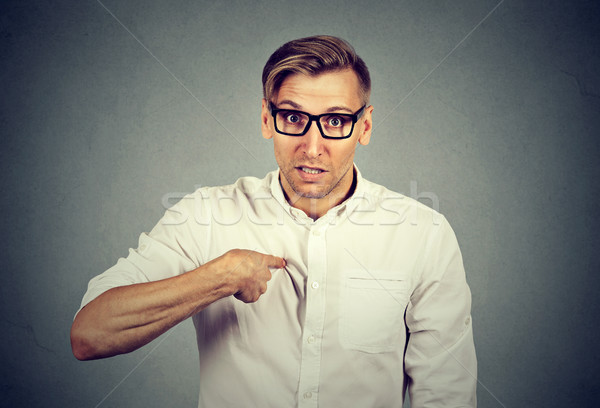 Stock photo: angry, mad, unhappy guy pointing at himself you mean me