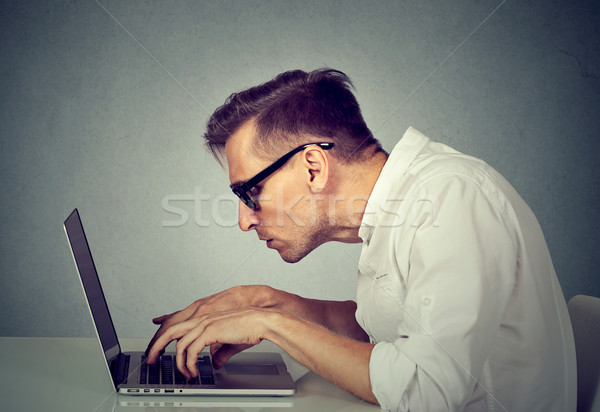 Stock photo: young man in glasses working on computer sitting at desk