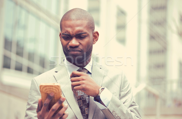 Unhappy young man talking texting on cellphone outdoors Stock photo © ichiosea