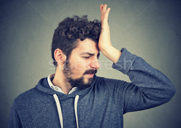 silly regretful young man, slapping hand on head having a duh moment Stock photo © ichiosea