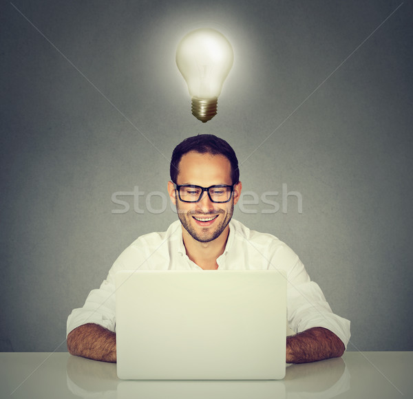 Happy man working sitting at desk, looking at laptop computer Stock photo © ichiosea