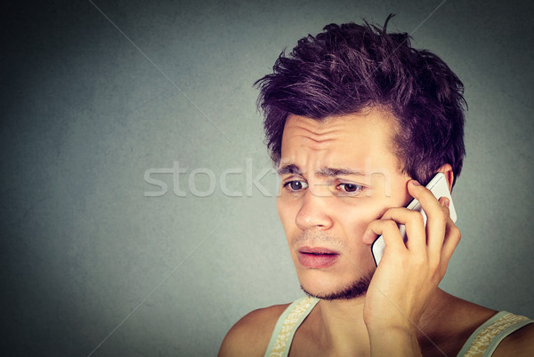 worried young man talking on phone to someone looking upset Stock photo © ichiosea