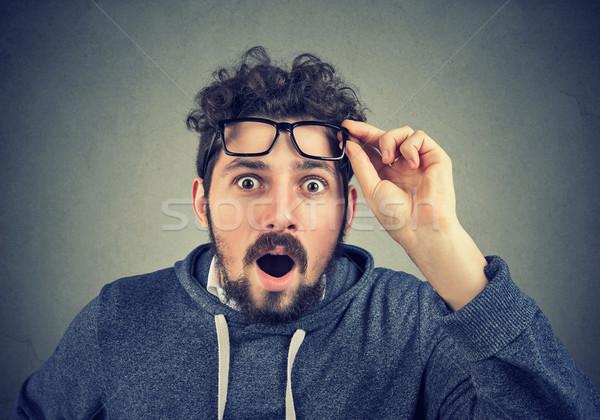 Shocked man taking off eyeglasses  Stock photo © ichiosea