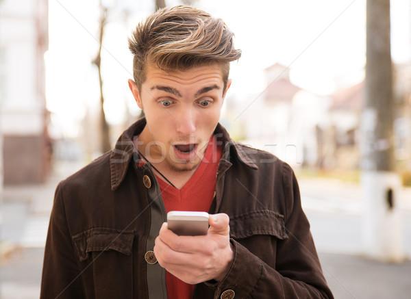 Amazed man reading phone outside Stock photo © ichiosea