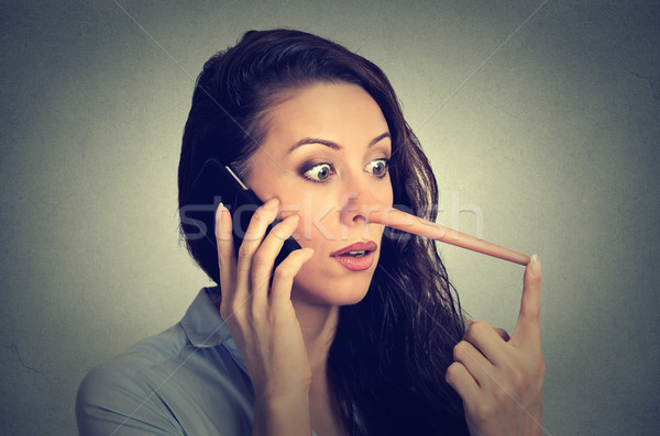 shocked woman with long nose talking on mobile phone. Liar concept Stock photo © ichiosea