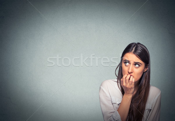 Young hesitant nervous woman biting fingernails craving or anxious Stock photo © ichiosea