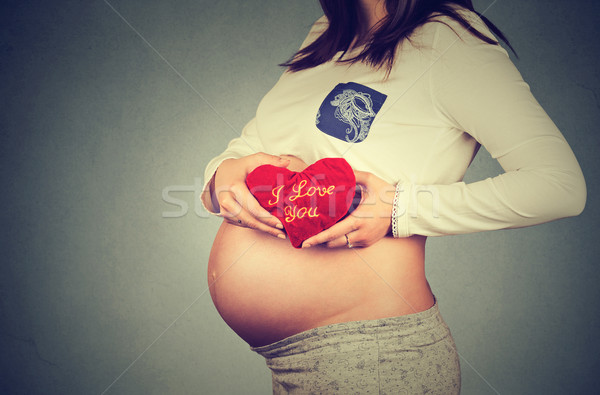 pregnant woman's belly with heart shaped red pillow. Human pregnancy concept  Stock photo © ichiosea