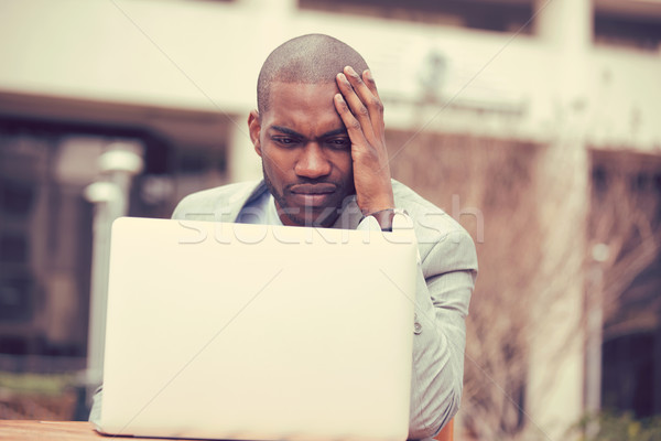 stressed businessman sitting outside corporate office working on laptop Stock photo © ichiosea