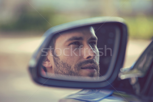 Side mirror reflection of a young man driving his new car Stock photo © ichiosea