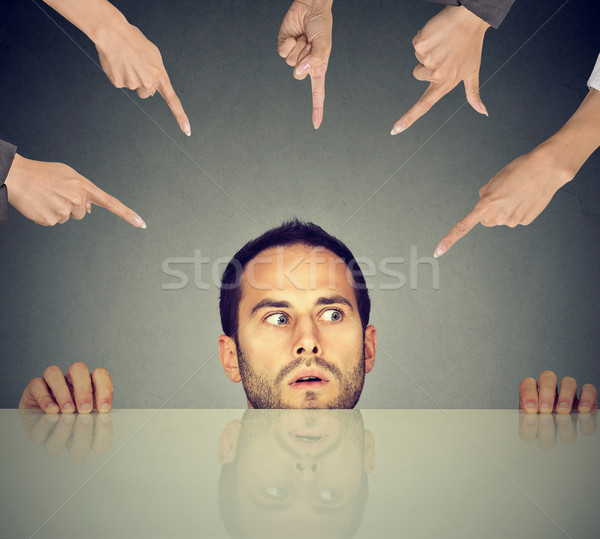 Scared man young employee hiding under the table being accused by many people who point fingers at h Stock photo © ichiosea